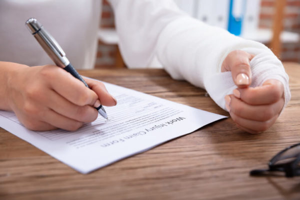 person with arm cast signing a document